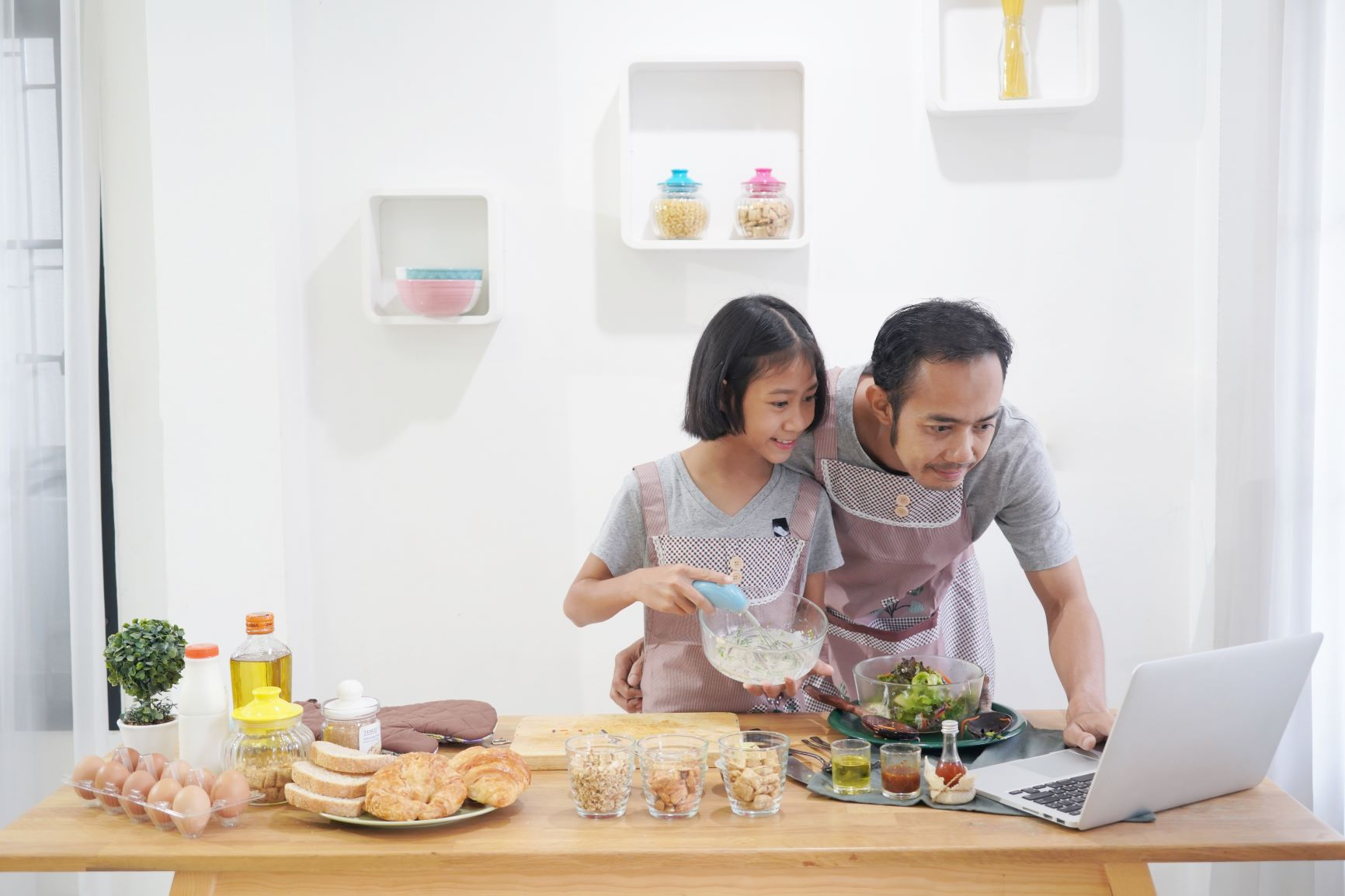 dad and daughter learning cooking online web